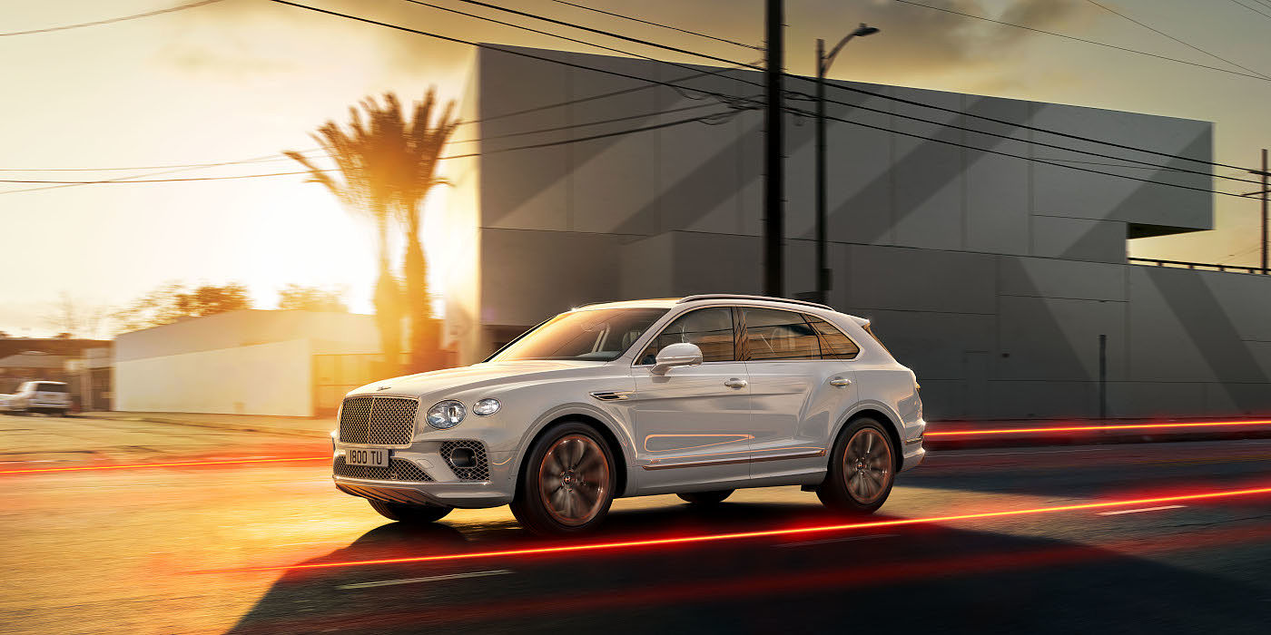 new-bentley-bentayga-hybrid-in-ice-white-paint-front-three-quarters-driving-past-buildings-in-los-angeles