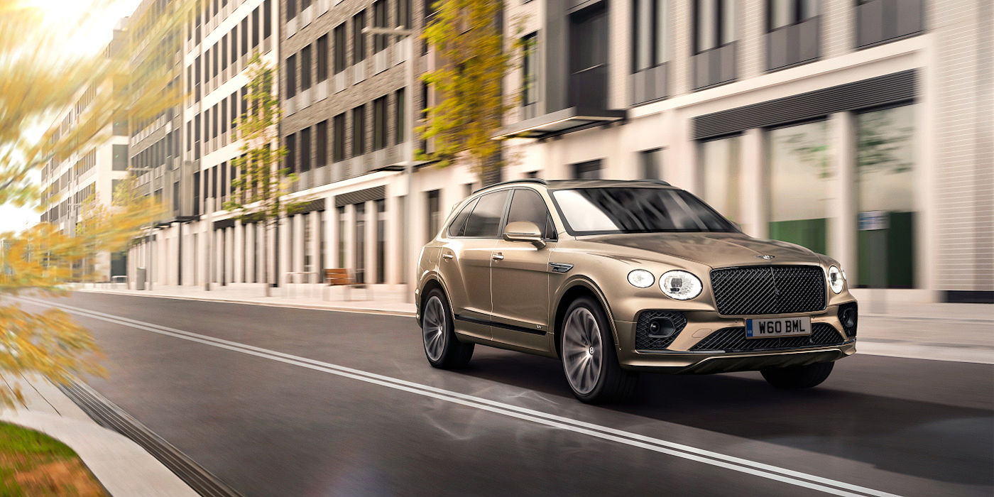 new-bentley-bentayga-hybrid-in-patina-paint-front-three-quarters-driving-through-london